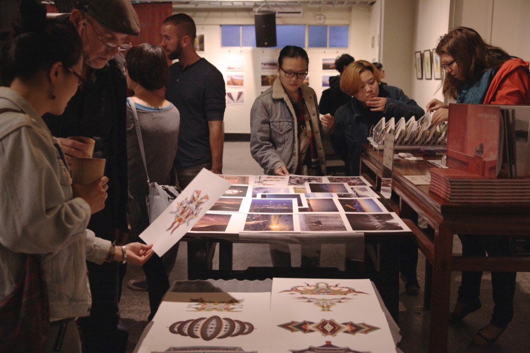 Red Roomers browse through Houghton's prints and peruse his book at the opening of Red Room's third Visual Dialogues