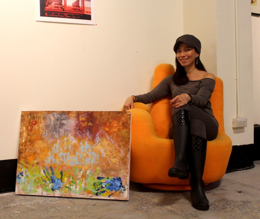 Artist Kate Huang sits next to the finished painting.