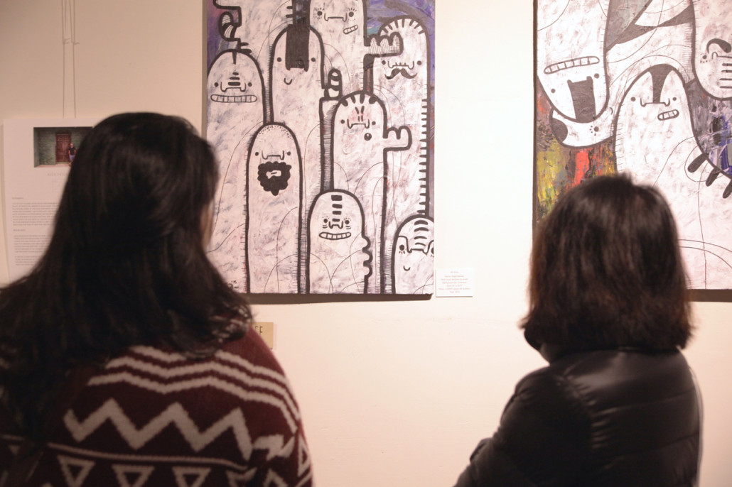 Two attendees pause to take in a view of Bara's artwork at the opening night of Visual Dialogues 3.