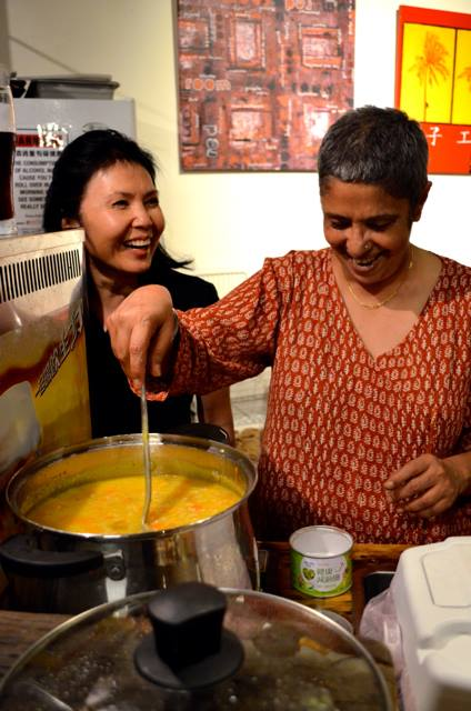 Roma Mehta and Sharon Landon laugh while preparing the stone soup for Red Roomers